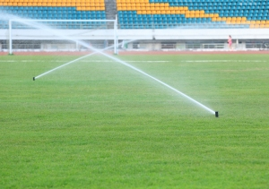 watering green grass on football field